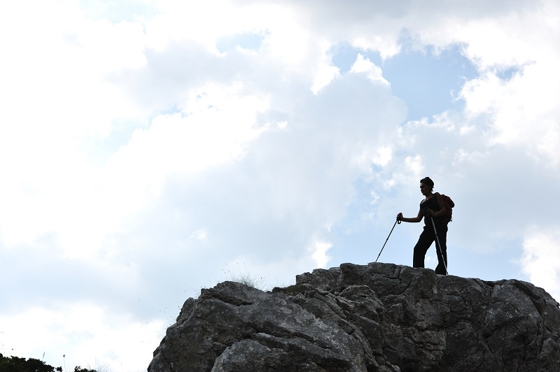 silhouette of a woman during and adventage climbing and mountain walking_BtEJoKpSo