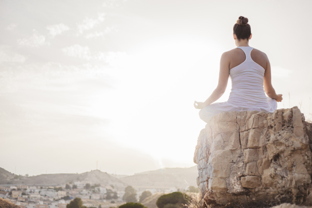 peaceful-woman-meditating-at-sunset_23-2147662229