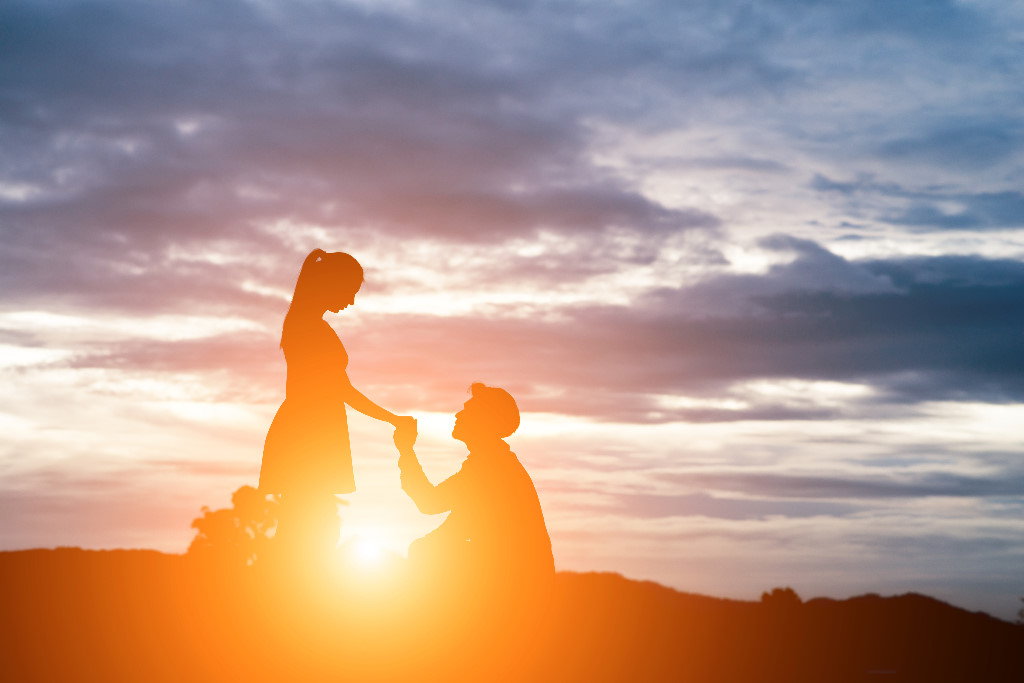 silhouette of man ask woman to marry on  mountain background.